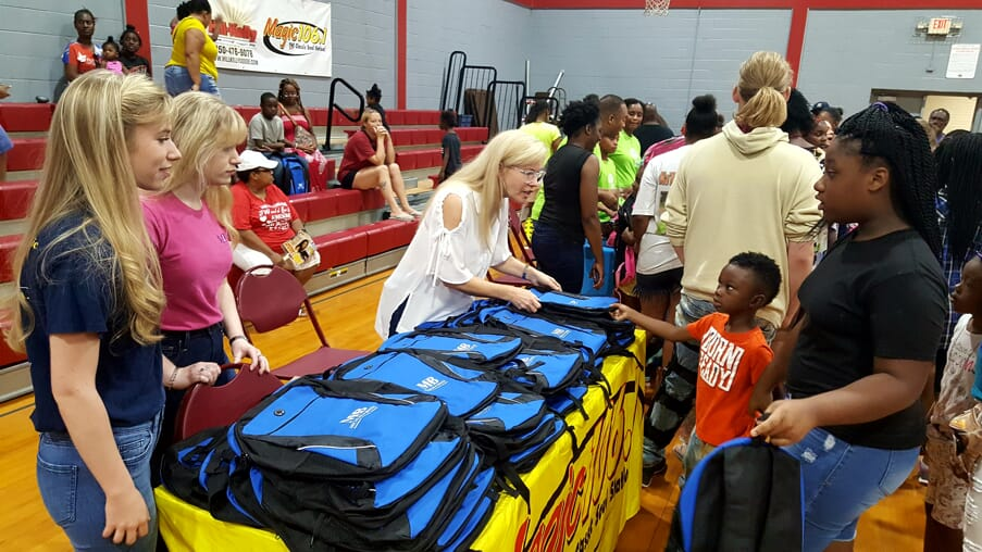 Michles & Booth handing out backpacks