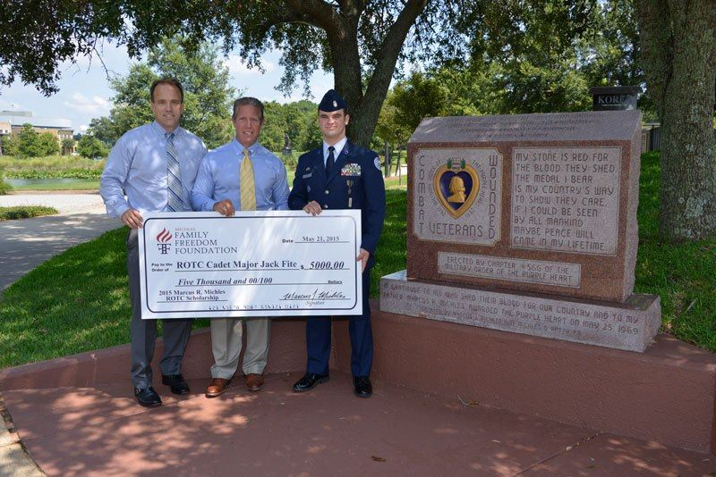 Michles & Booth attorneys Marcus Michles (center) and Chris Janes (left) present the 2nd Annual Marcus R. Michles ROTC Scholarship to Cadet Major Jack Fite in front of the Purple Heart Memorial in Pensacola, which – like the scholarship – also honors Michles' father.